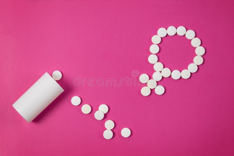 Здоровье концепции женское Символ рода сделанный из розовых таблеток или планшетов на розовой предпосылке стоковая фотография