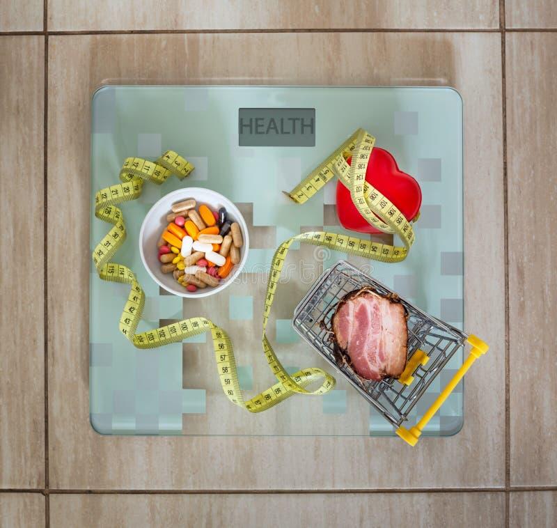 здоровье планшеты, сердце вместе с жирной пищей как концепция полного, плохого питания или стимул к здоровому lifestyl стоковые изображения