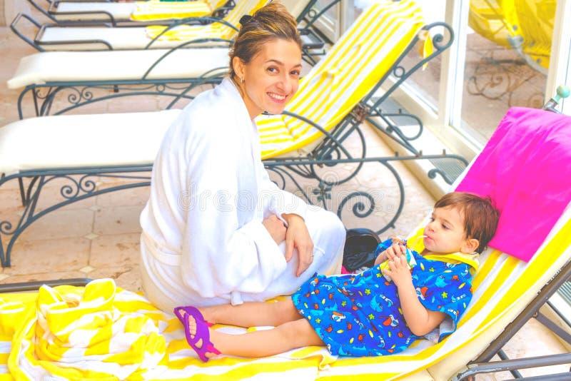 Здоровье ребенка курорта матери и младенца ослабляя на фруктовом соке deckchair выпивая стоковое фото