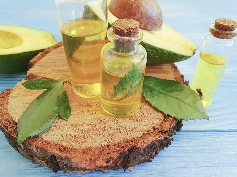 Здоровье эфирного масла красоты бутылки свежего авокадоа органическое голубая деревянная предпосылка, органический противостарите стоковая фотография