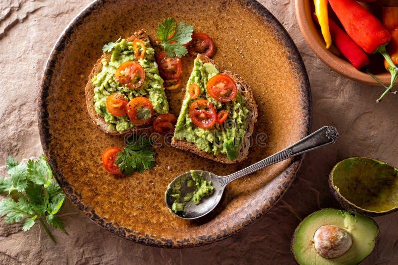 Здравица авокадоа с отрезанным томатом стоковое фото