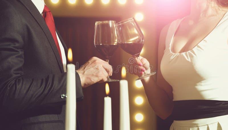Здравица пар clink стекла с красным вином стоковые изображения