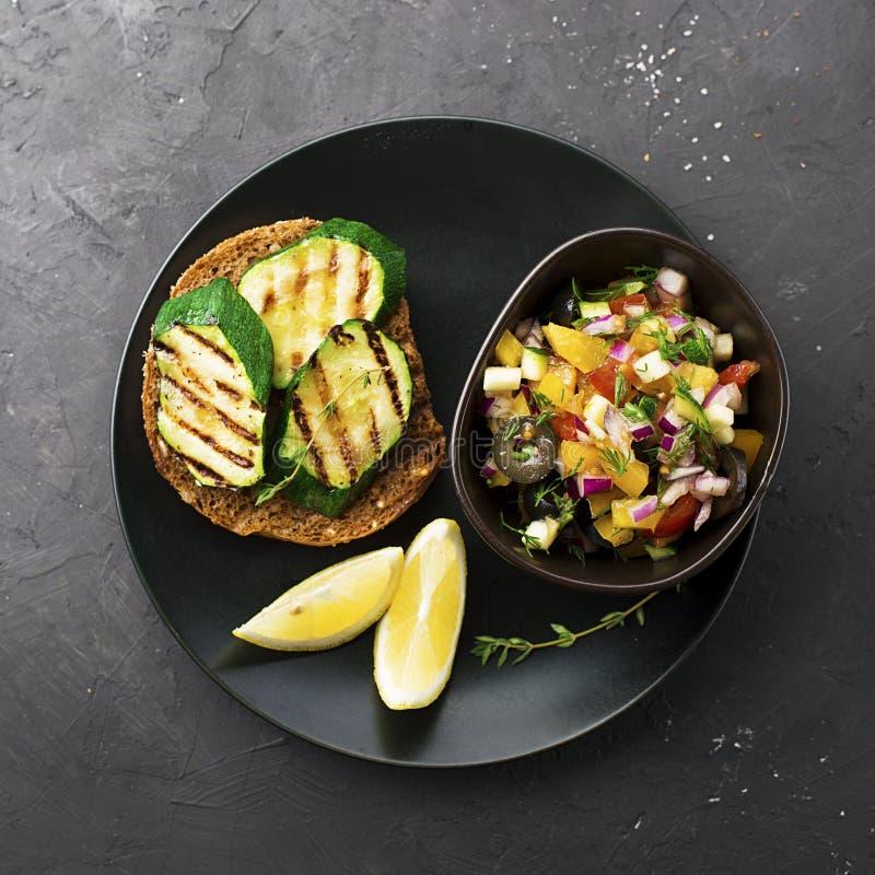 Здравица с грилем цукини и салат оливок, огурцов, томата, сладостного красного лука, желтого перца chili с зажаренный стоковое фото rf