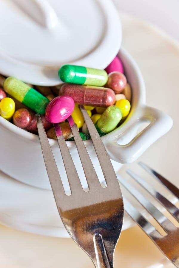 Здравоохранение и здоровье - пилюльки диеты и вес освобождать - различные таблетки в баке с вилками стоковое изображение rf