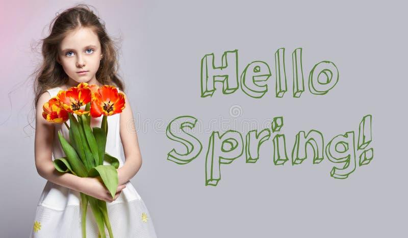 Здравствуйте! весна, 8-ое марта Девушка моды рыжеволосая с тюльпанами в руках Фото студии на предпосылке покрашенной светом прогу стоковые фотографии rf