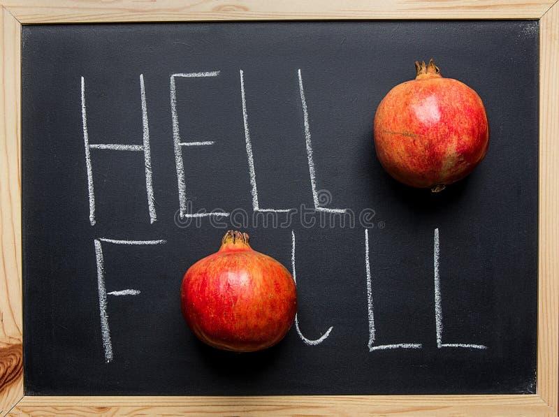 Здравствуйте! оформление литерности руки падения с зрелыми красными гранатовыми деревьями на черной доске Благодарение сбора осен стоковое изображение rf