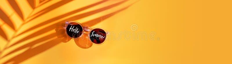 Здравствуйте слово лета на тени лист ладони с солнечными очками лета на желтой предпосылке в солнечном свете в каникулах праздник стоковые фотографии rf