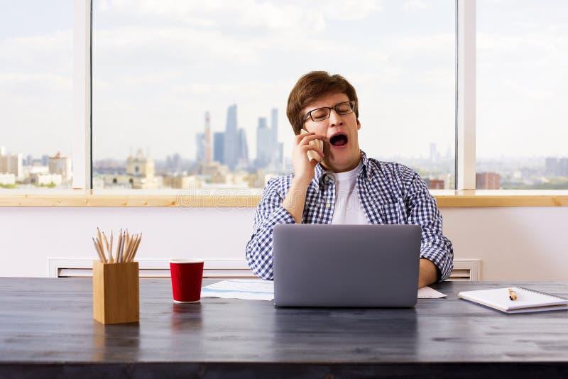 Зевая человек на телефоне стоковое изображение