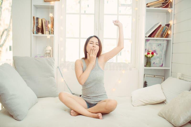 Зевок женщины на кровати дома стоковое фото rf