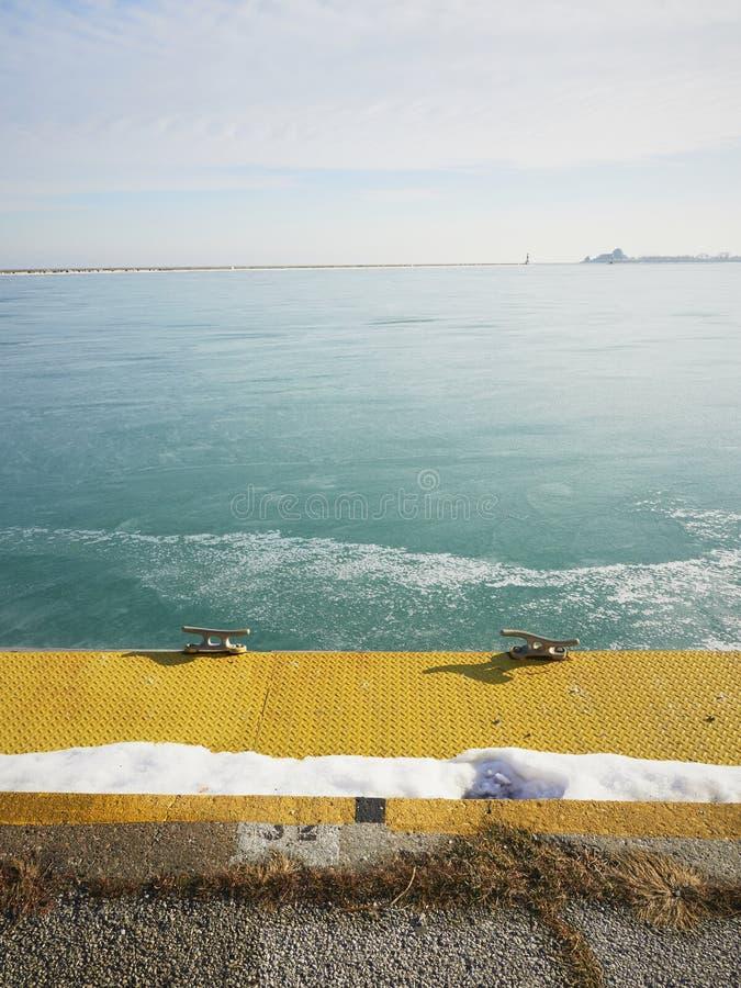 Зеленая вода океана в зиме Желтая пристань со снегом стоковая фотография