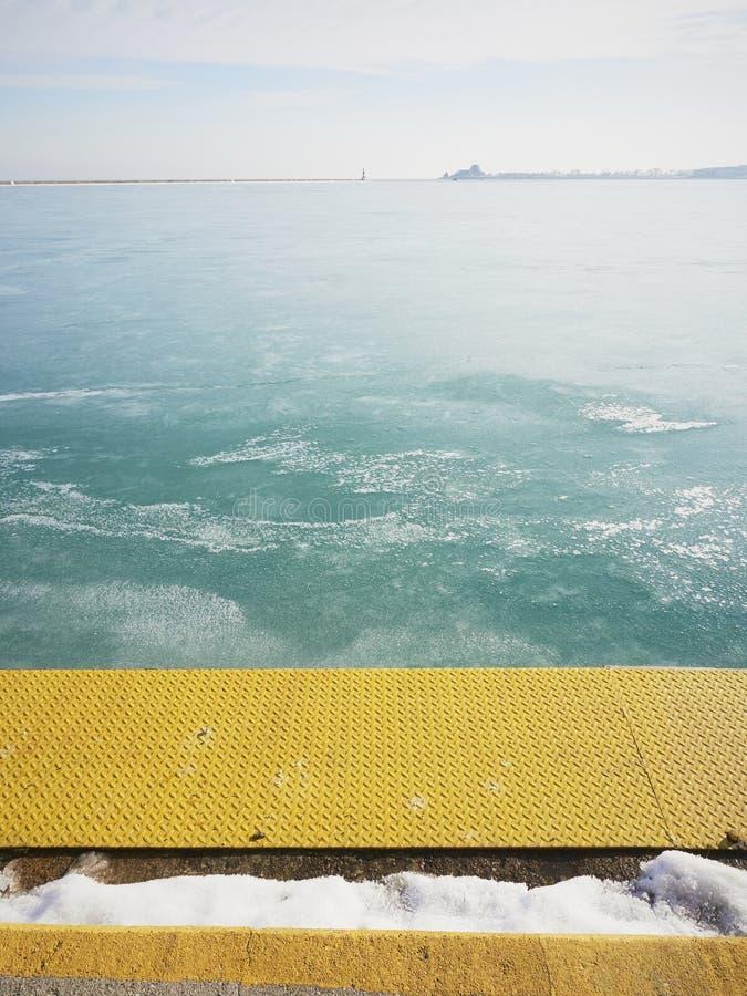 Зеленая вода океана в зиме Желтая пристань со снегом стоковое фото rf