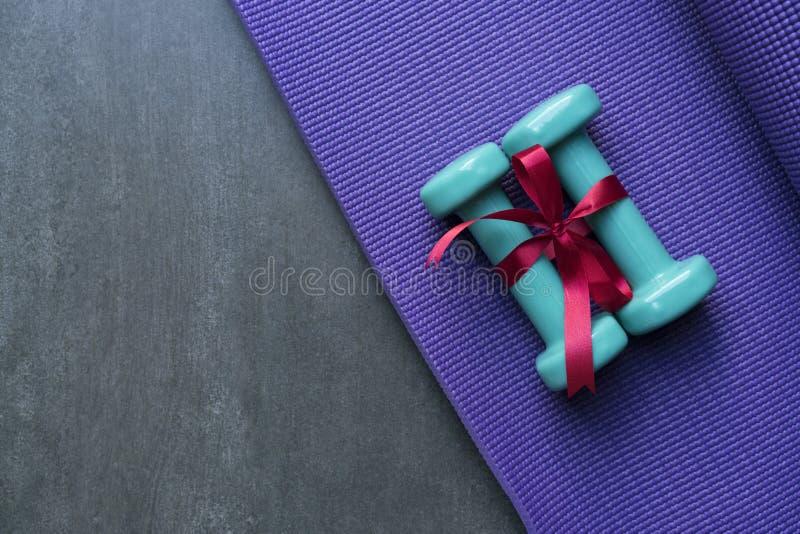 Зеленая гантель 2 с красным смычком подарка на предпосылке циновки йоги стоковая фотография rf
