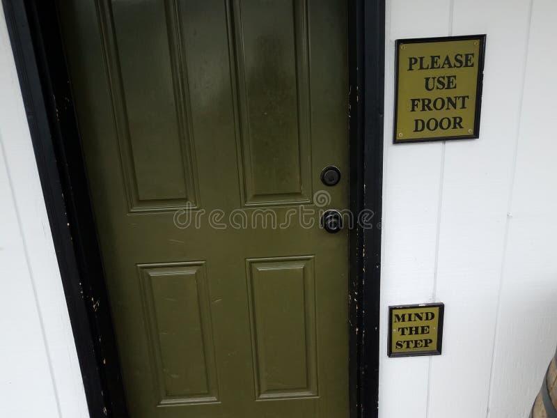 Зеленая дверь с пожалуйста использует парадный вход и запомнить знаки шага стоковые изображения rf