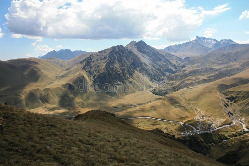 Зеленая долина в горах Кавказа с змейчатой дорогой, Россией стоковые изображения rf
