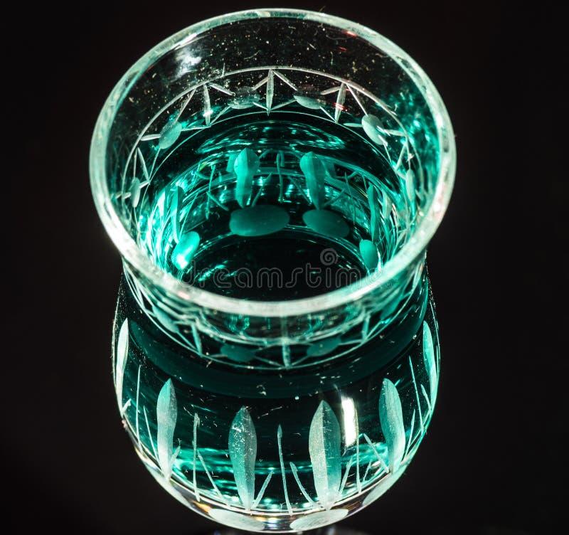Зеленая жидкость в кристаллическом стекле с темной предпосылкой стоковое изображение