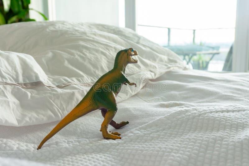 Зеленая и желтая пластиковая игрушка динозавра на кровати родителя показывая родной дом где дети живут стоковое фото