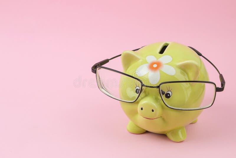 Зеленая копилка со стеклами на яркой розовой предпосылке Финансы, сбережения, деньги E стоковые изображения