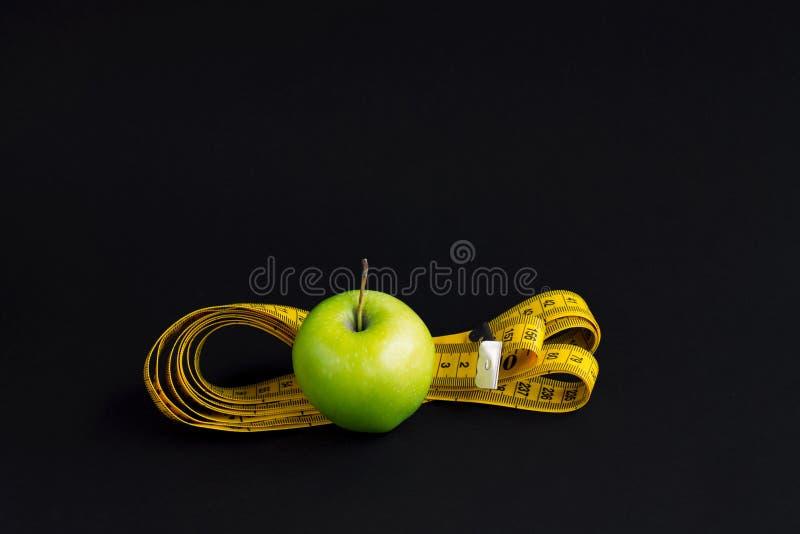 Зеленая лента яблока, белых и измерять с сантиметрами и дюймами изолированная на черной предпосылке стоковое изображение rf