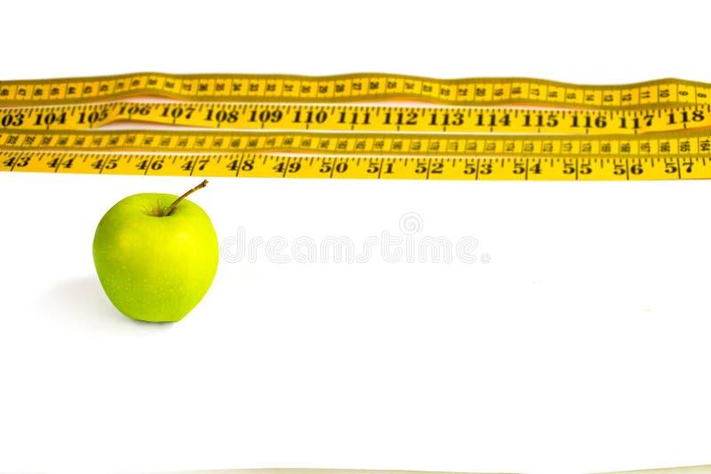 Зеленая лента яблока и blure измеряя с сантиметрами и дюймами стоковая фотография