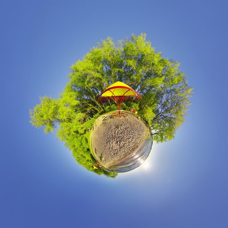 Зеленая маленькая планета с деревьями и мягким голубым небом Крошечный заход солнца планеты на пляже угол наблюдения 360 звезды п стоковая фотография