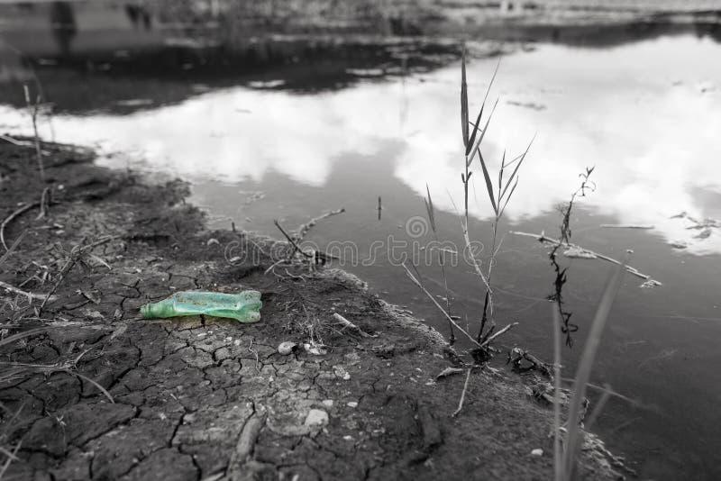 Зеленая пластиковая бутылка в monochrome береге озера стоковые изображения