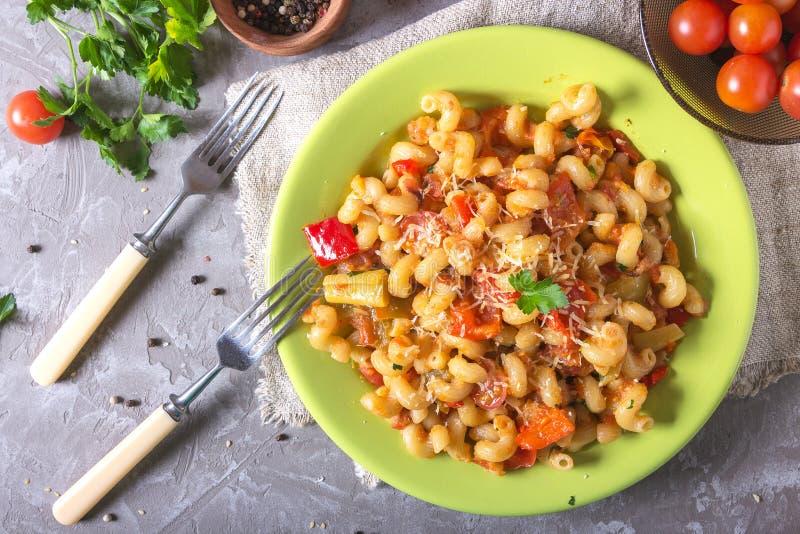 Зеленая плита вполне со свежих домодельных макаронных изделий макарон локтя, частей болгарского перца, половин томата вишни, заск стоковые фотографии rf