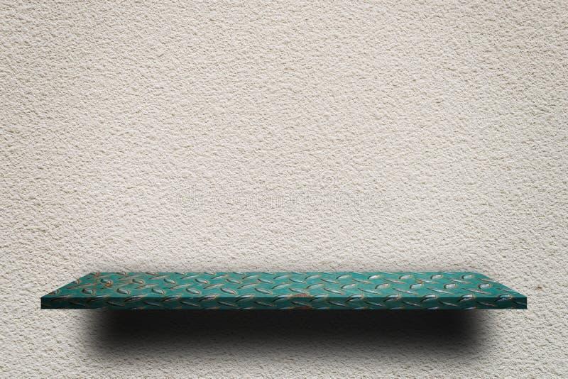 Зеленая полка металла на грубой серой стене цемента стоковые фото