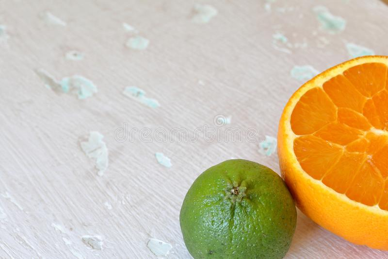 Зеленая сочная известка и половина апельсина На затрапезной достигшей возраста предпосылке стоковые фото