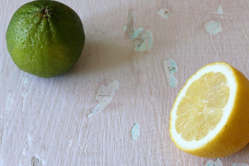 Зеленая сочная известка и половина лимона На затрапезной достигшей возраста предпосылке стоковая фотография rf