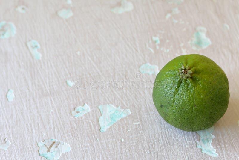 Зеленая сочная известка На затрапезной достигшей возраста предпосылке стоковые фото