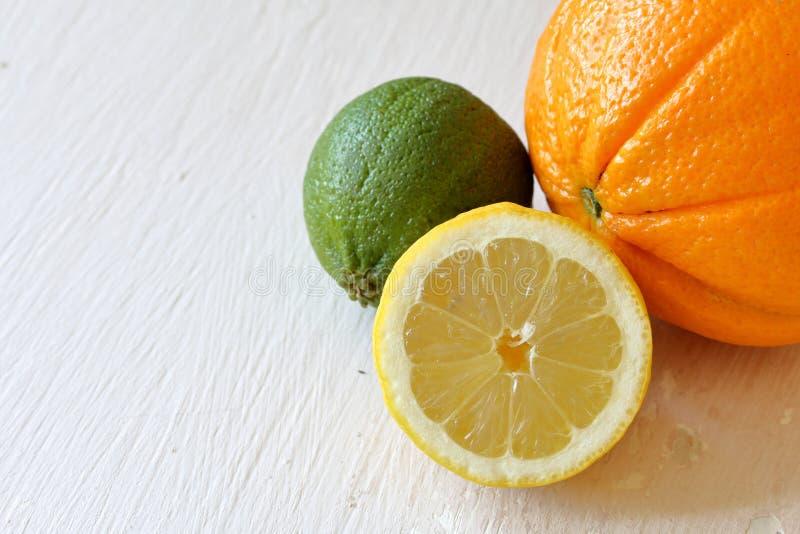 Зеленая сочная известка, оранжевый и половинный лимон На затрапезной достигшей возраста предпосылке стоковые изображения