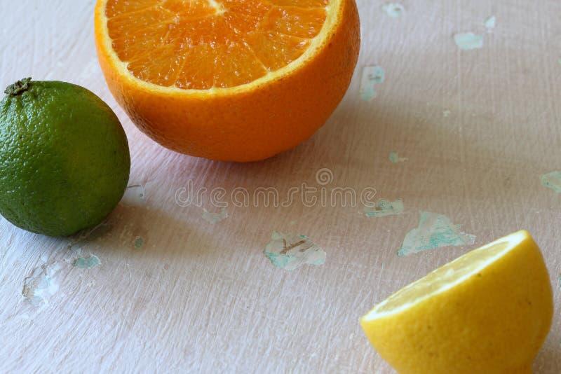 Зеленая сочная известка, оранжевый и половинный лимон На затрапезной достигшей возраста предпосылке стоковые фото