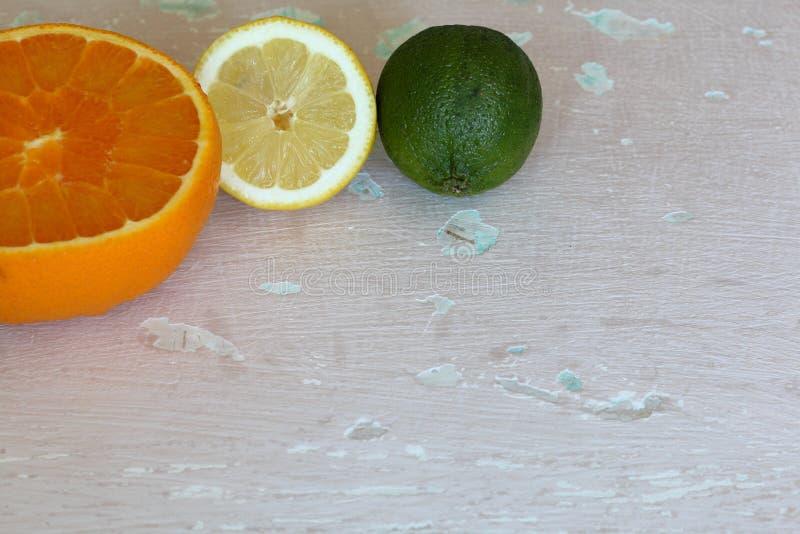 Зеленая сочная известка, оранжевый и половинный лимон На затрапезной достигшей возраста предпосылке стоковая фотография