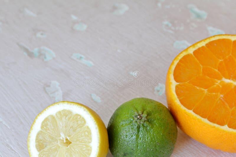 Зеленая сочная известка, оранжевый и половинный лимон На затрапезной достигшей возраста предпосылке стоковые фотографии rf
