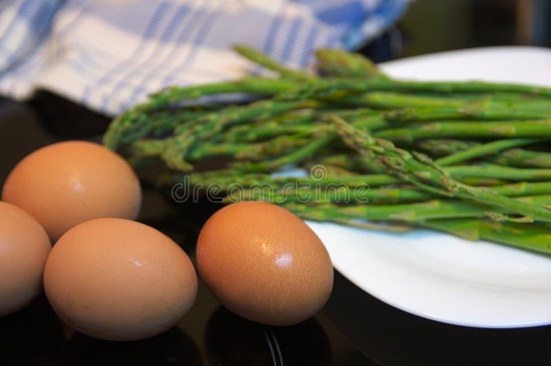 Зеленая спаржа и коричневые яичка в белом блюде стоковая фотография