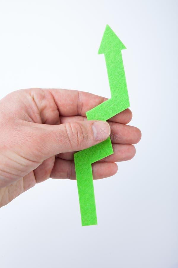 Зеленая стрелка вверх в руке на белой предпосылке Везение и рост стоковые фото
