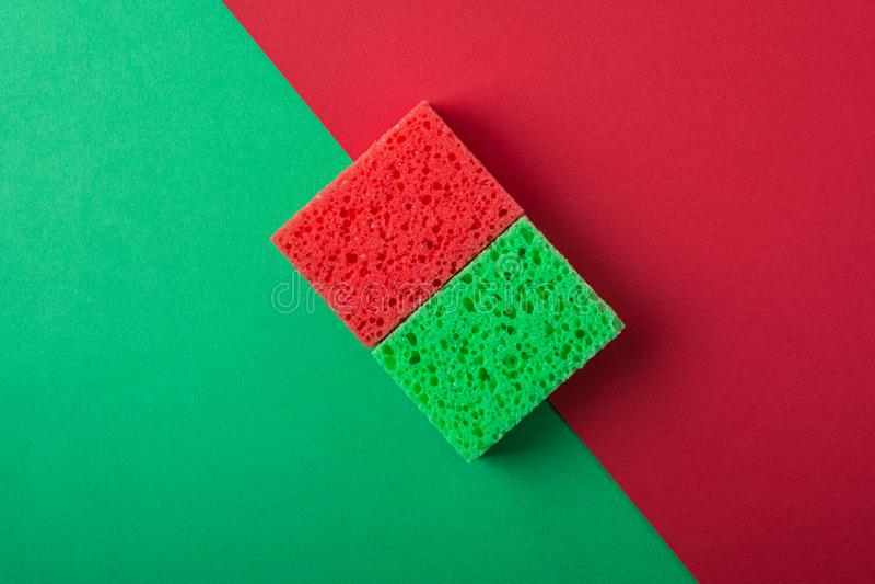 2 зеленое и красные губки на зеленой и красной покрашенной бумажной предпосылке, космосе экземпляра, взгляде сверху, плоском поло стоковые фото