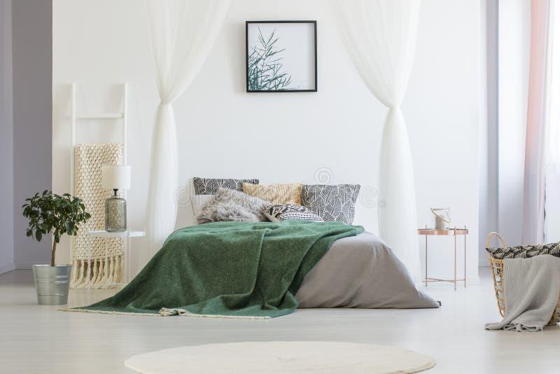 Зеленое одеяло брошенное на двуспальную кровать с много подушками и серых sh стоковое фото rf