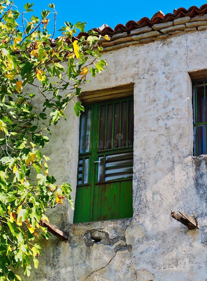 Зеленое окно на старом греческом доме в деревне стоковые фотографии rf