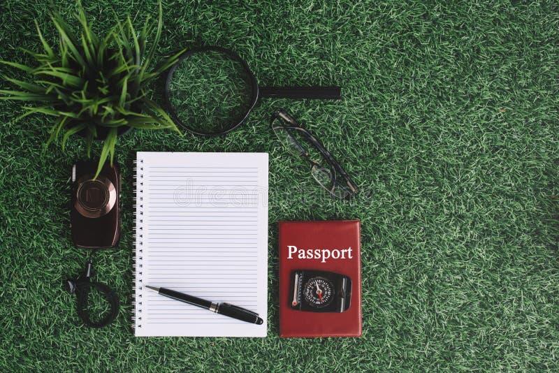 Зеленое растение, камера, лупа, компас, пасспорт и пустая тетрадь на зеленой траве стоковое изображение rf