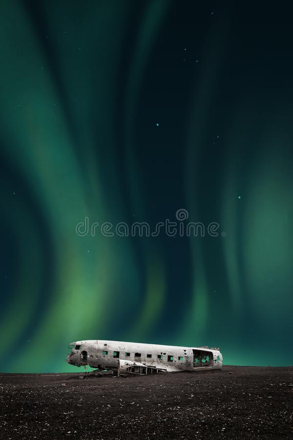 Зеленое северное сияние над развалиной белого самолета стоковая фотография rf