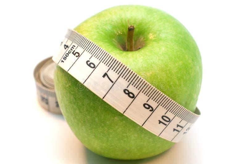 Зеленое яблоко в оболочке путем измерять ленту изолированную на белой предпосылке стоковые изображения rf