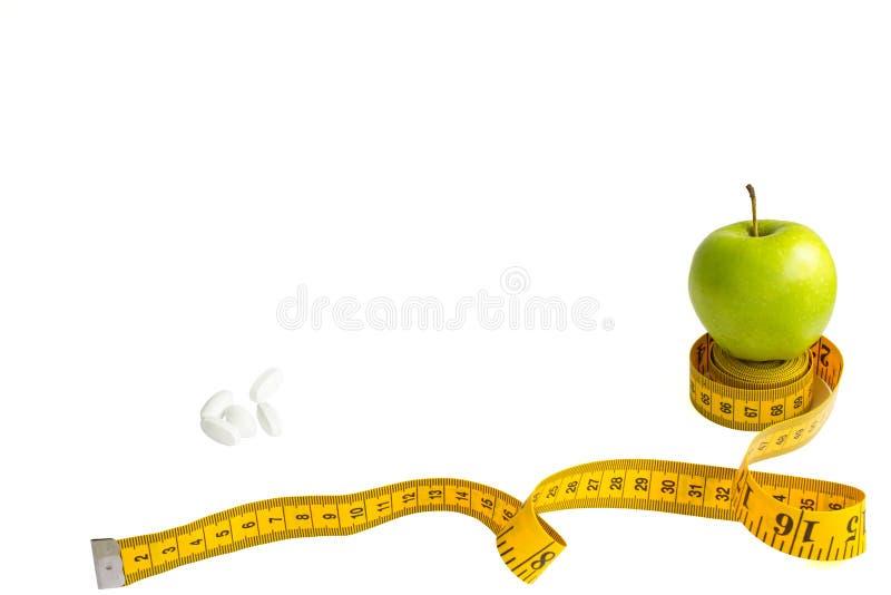 Зеленое яблоко, измеряя лента с корками сантиметров и дюйма и белых изолированными на белой предпосылке стоковые изображения