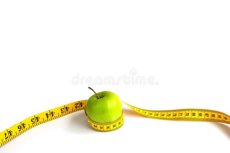 Зеленое яблоко и измеряя лента с сантиметрами и дюймами стоковое фото