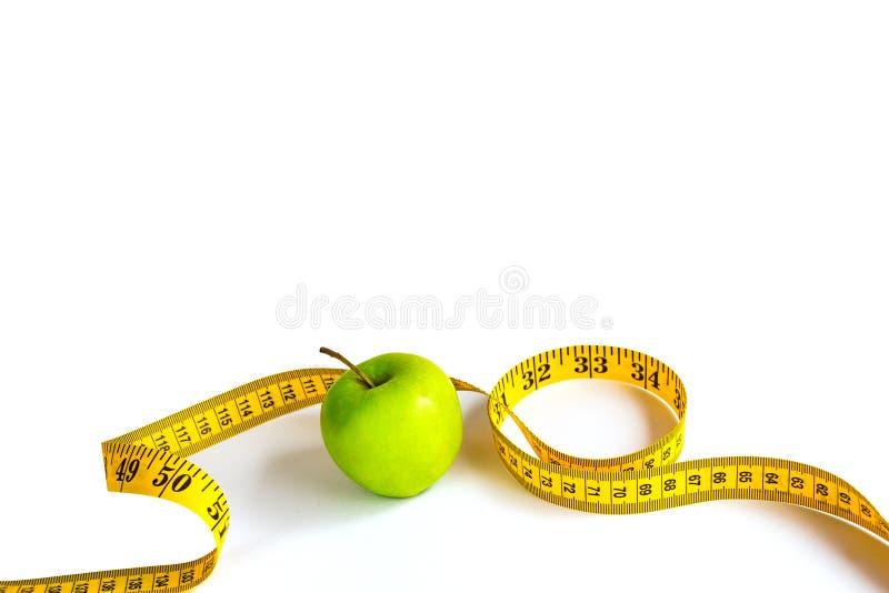 Зеленое яблоко и измеряя лента с сантиметрами и дюймами стоковые изображения rf