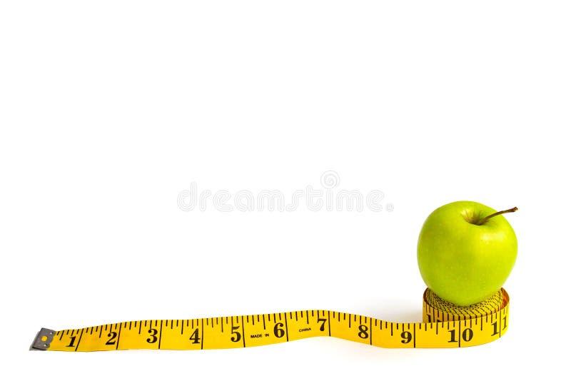 Зеленое яблоко и измеряя лента с сантиметрами и дюймами стоковые фотографии rf