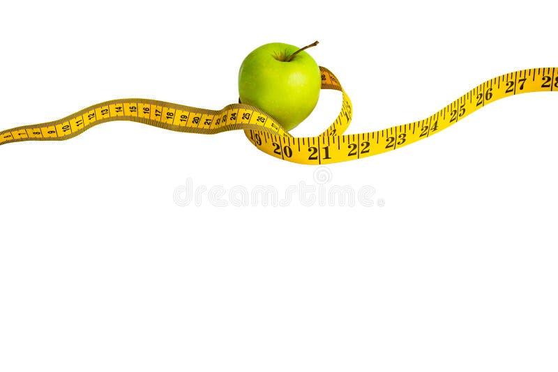 Зеленое яблоко и измеряя лента с сантиметрами и дюймами стоковое фото rf