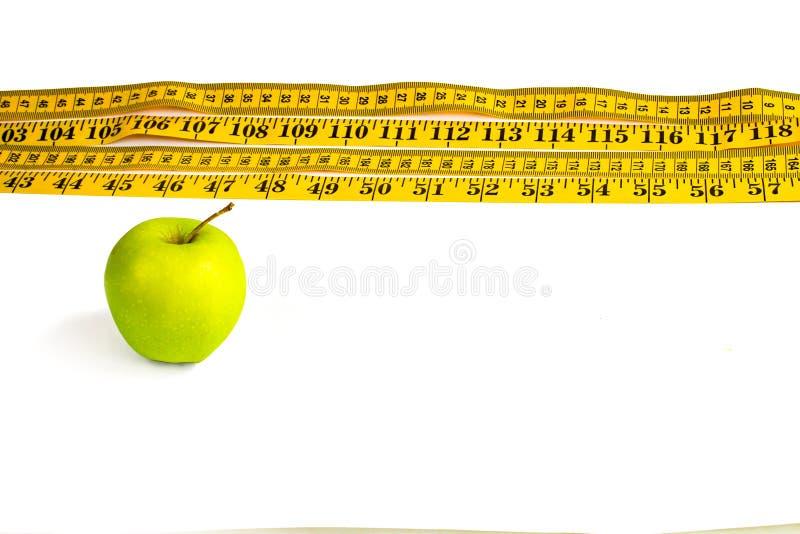 Зеленое яблоко и измеряя лента с сантиметрами и дюймами стоковые изображения