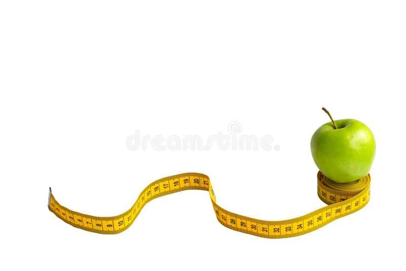 Зеленое яблоко и измеряя лента с сантиметрами и дюймами изолированные на белой предпосылке стоковые изображения