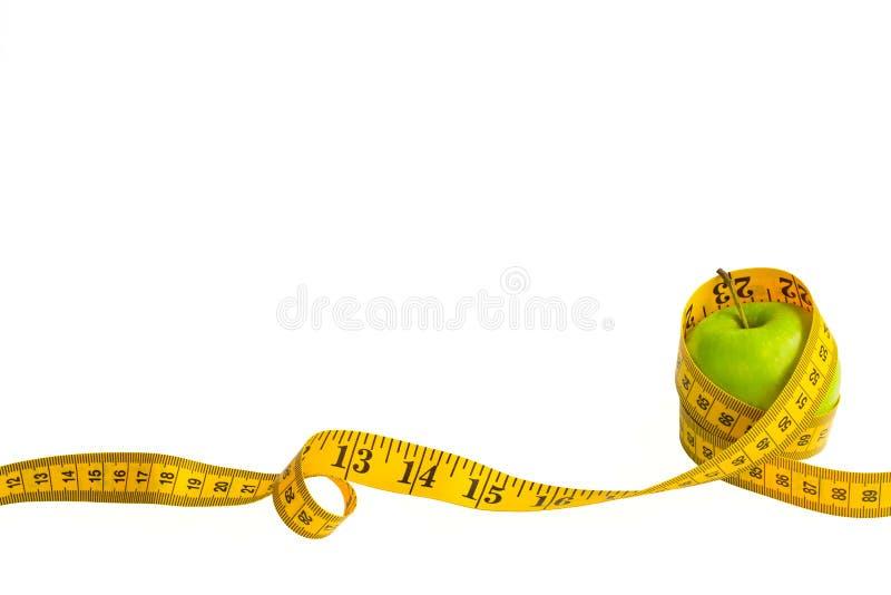 Зеленое яблоко и измеряя лента с сантиметрами и дюймами изолированные на белой предпосылке стоковое изображение